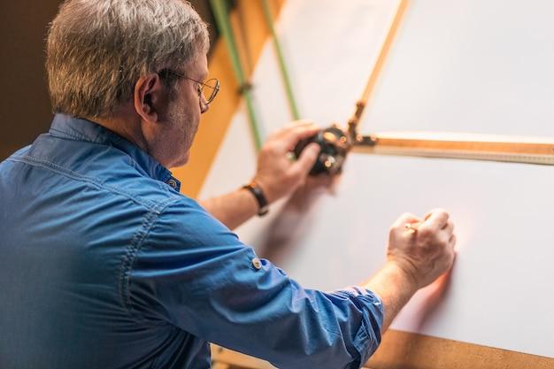 Ingeniero creativo maduro trabajando con proyecto en tablero de dibujo Foto gratis