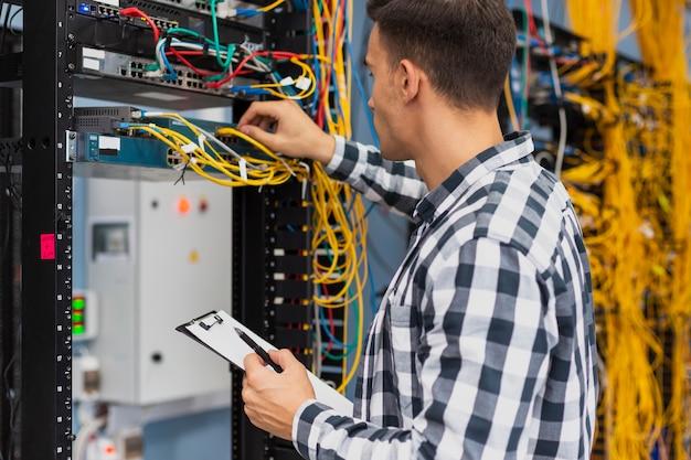 Ingeniero eléctrico trabajando en conmutador de red Foto gratis