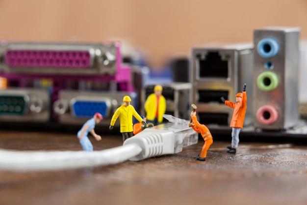 Ingeniero En Miniatura Y El Trabajador Plug In De Lan Por