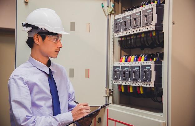 El ingeniero es verificar el voltaje o la corriente mediante un voltímetro en el panel de control de la planta de energía. Foto Premium