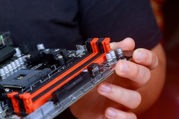 El ingeniero de instalación de memoria ram en la placa base del ordenador en el laboratorio de computación. Foto Premium