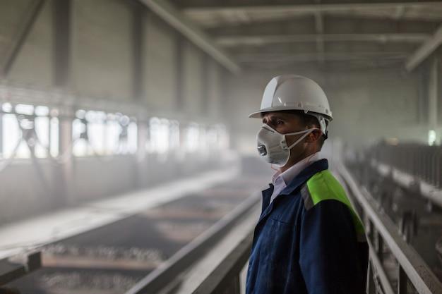 Ingeniero de minas en casco blanco y respirador inspecciona taller sucio y polvoriento Foto Premium