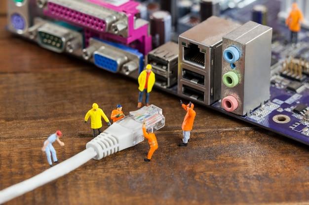 Ingeniero en miniatura y el trabajador plug-in de lan por cable a la computadora Foto gratis