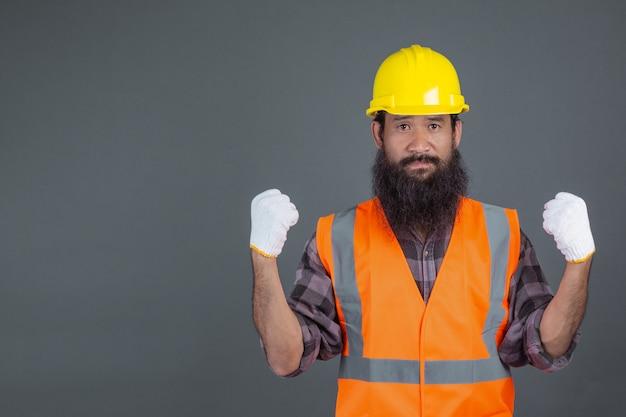 Un ingeniero que llevaba un casco amarillo con guantes blancos mostró un gesto en un gris. Foto gratis