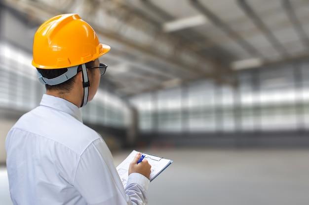 Ingeniero de sexo masculino que comprueba la fábrica con la nota en el bloc de notas o la industria Foto Premium