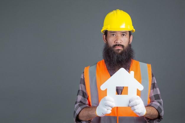 Un ingeniero de sexo masculino que lleva un casco de seguridad amarillo que lleva a cabo un símbolo de la casa blanca en un gris. Foto gratis
