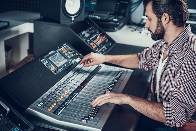 Ingeniero de sonido con mesa de mezclas de estudio. Foto Premium