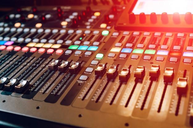 Ingeniero de sonido remoto. muchos botones de la consola de mesa de mezclas de audio negro. equipo de musica. de cerca Foto Premium
