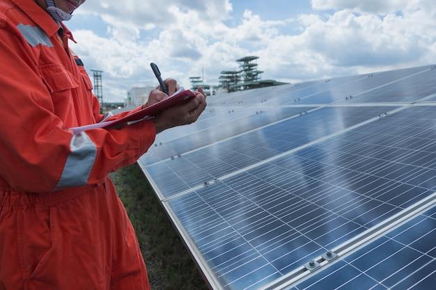 Ingeniero trabajando en la verificación y mantenimiento de equipos eléctricos en la planta de energía solar; ingeniero revisando el panel solar en operación de rutina en la planta de energía solar Foto Premium