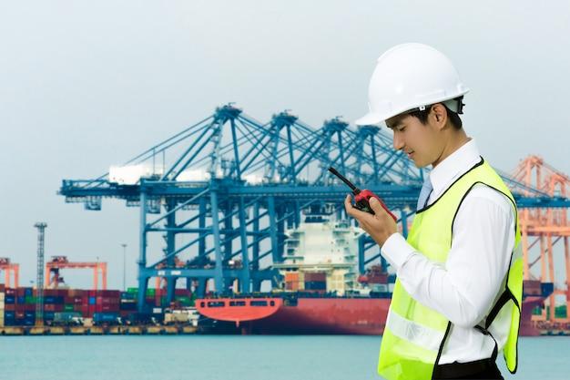 Ingenieros asiáticos para los hombres del puerto marítimo. usando la radio con el trabajo todo el tiempo. Foto Premium