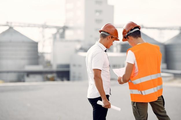 Ingenieros en cascos de pie junto a la fábrica. Foto gratis