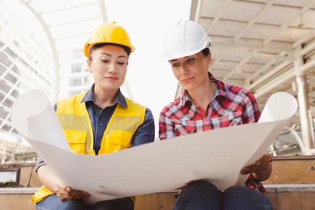 ingenieros-dos-mujeres-trabajando-plan-construccion-papel-ciudad_39730-712