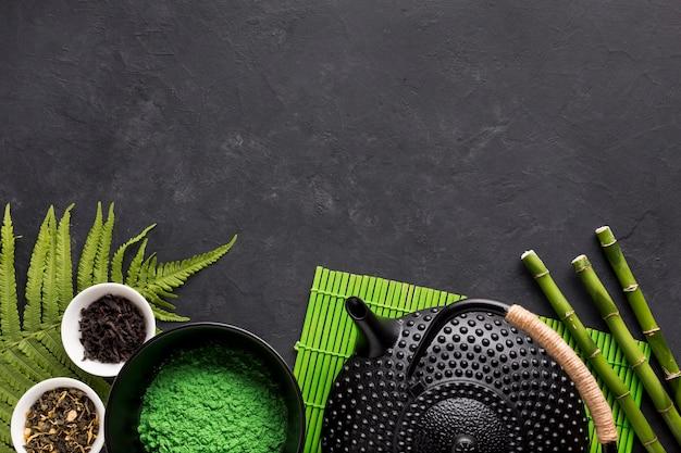 Ingrediente crudo de la infusión de hierbas con la tetera en fondo negro Foto gratis