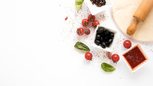 Ingrediente de la pizza con pan de la pizza y rodillo sobre aislado en el fondo blanco Foto gratis