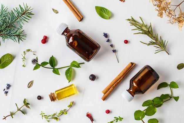 Ingredientes para aceites esenciales. diferentes hierbas y botellas de aceite esencial, fondo blanco, flatlay. Foto Premium