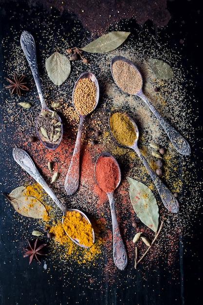 Ingredientes de especias alimenticias para cocinar fondo oscuro Foto Premium