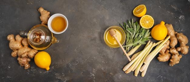 Ingredientes frescos jengibre, hierba de limón, salvia, miel y limón para un té de jengibre antioxidante y antiinflamatorio saludable sobre fondo oscuro con espacio de copia. vista superior. Foto Premium
