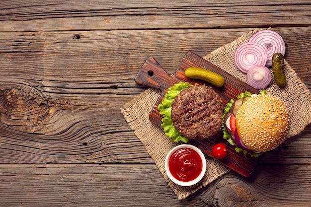 Ingredientes de la hamburguesa vista superior en una tabla de cortar Foto gratis