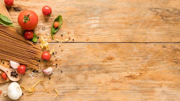 Ingredientes italianos crudos frescos con pasta de espagueti sobre mesa con textura Foto gratis