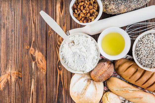 Ingredientes con panes recién horneados en la mesa de madera Foto gratis