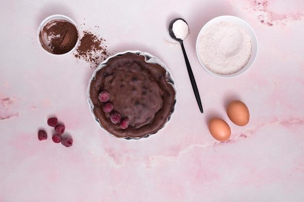 Ingredientes para pastel de chocolate con aderezos de frambuesa sobre fondo rosa Foto gratis