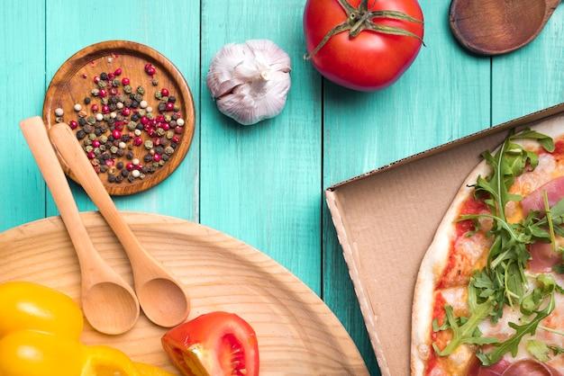 Ingredientes saludables en superficie con textura de madera con verduras y deliciosa pizza Foto gratis