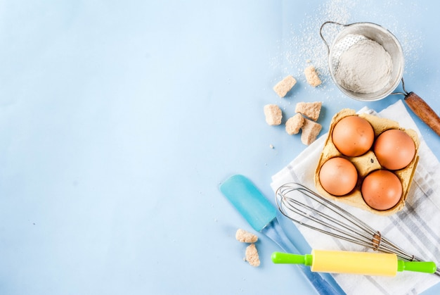 Ingredientes y utensilios para cocinar hornear huevo, harina, azúcar, batidor, rodillo Foto Premium