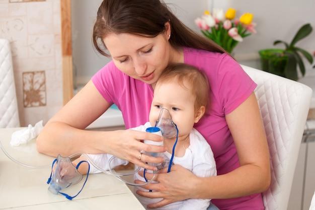La inhalación del niño hace a la mamá bebé Foto Premium