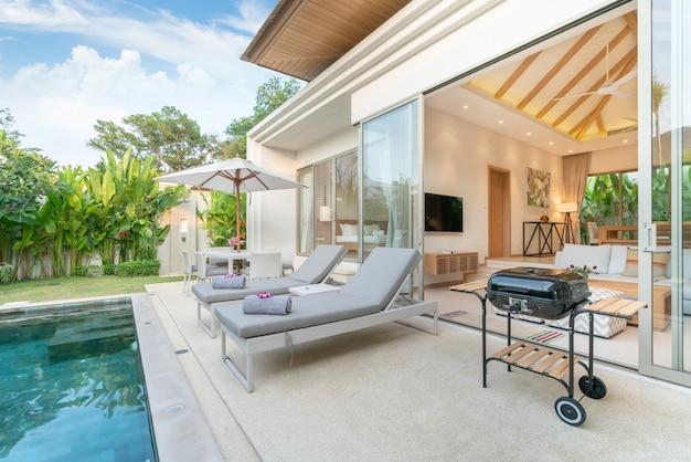 Inicio diseño de exteriores que muestra una villa con piscina tropical y jardín con vegetación. Foto Premium