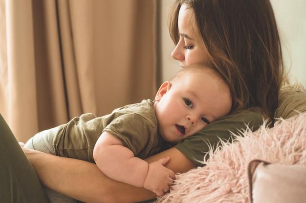 Inicio retrato de un bebé con la madre en la cama. mamá sosteniendo y besando a su hijo. concepto del día de la madre Foto Premium