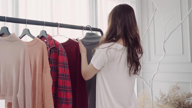 Inicio vestuario o tienda de vestuario vestuario. mujer joven asiática que elige su ropa del equipo de la moda Foto gratis