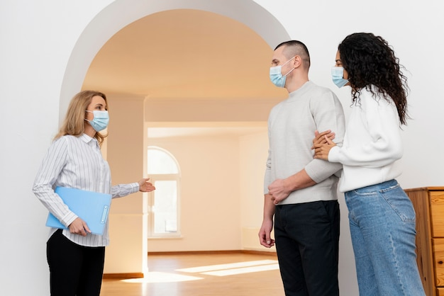 Inmobiliaria mujer con máscara médica mostrando pareja nueva casa Foto gratis