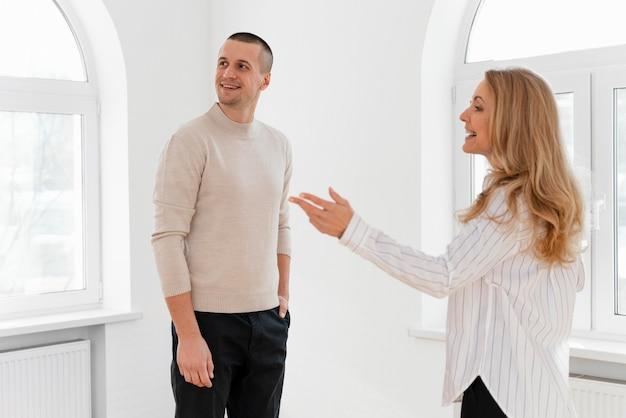 Inmobiliaria mujer mostrando hombre nueva casa Foto gratis