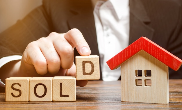 Una inmobiliaria tiene bloques con la palabra vendido. Foto Premium