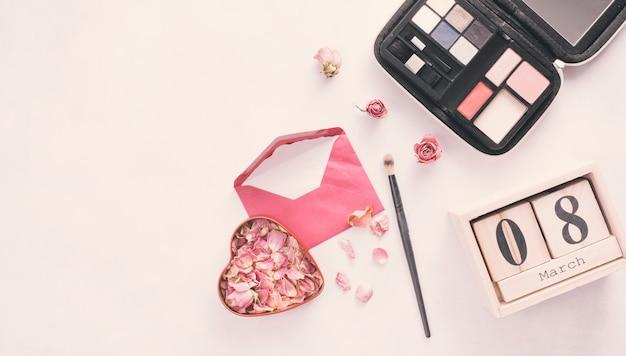 Inscripción del 8 de marzo con pétalos de rosa, sobre y sombras de ojos. Foto gratis