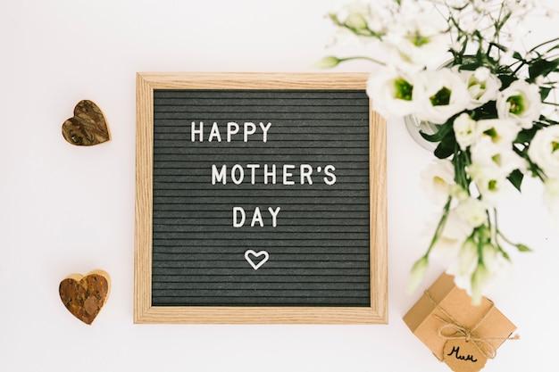 Inscripción del día de la madre feliz a bordo con flores Foto gratis