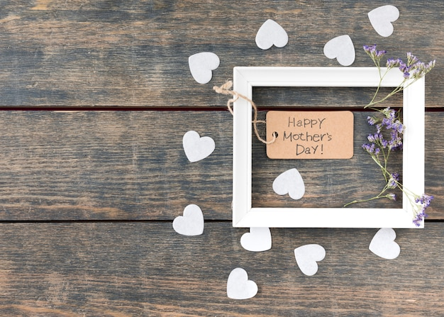 Inscripción del día de la madre feliz con flores y corazones pequeños Foto gratis