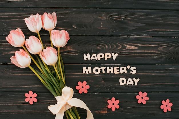 Inscripción del día de la madre feliz con ramo de tulipanes Foto gratis