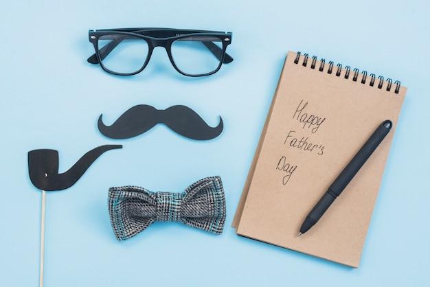 Inscripción del día del padre feliz en el bloc de notas con gafas y bigote Foto gratis