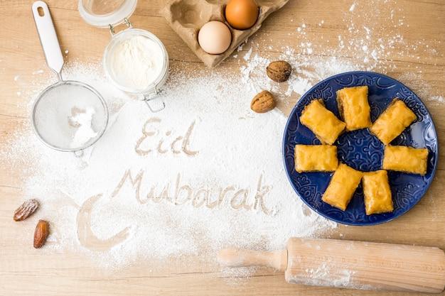 Inscripción de eid mubarak en harina con dulces del este en placa Foto gratis