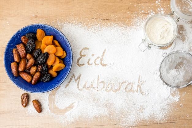 Inscripción de eid mubarak en harina junto a frutos secos. Foto gratis