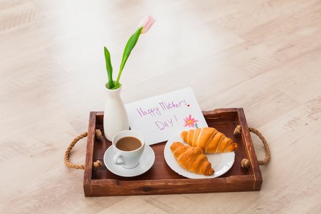 Inscripción feliz del día de las madres con café en bandeja Foto gratis