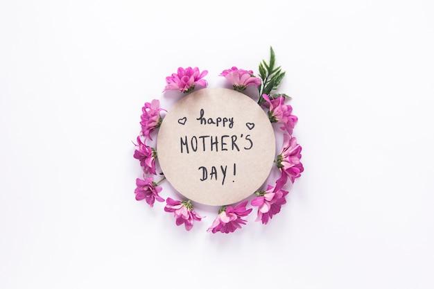 Inscripción feliz del día de madres con flores de color púrpura Foto gratis