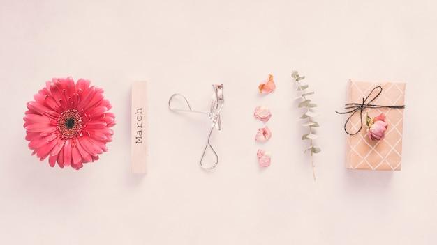 Inscripción de marzo con flores y caja de regalo en mesa Foto gratis