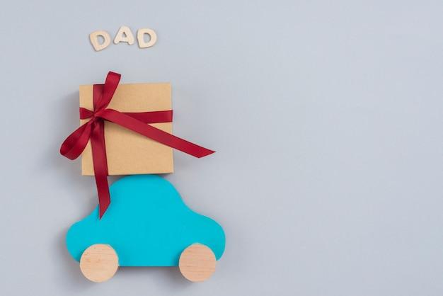 Inscripción de papá con caja de regalo y carro pequeño. Foto gratis