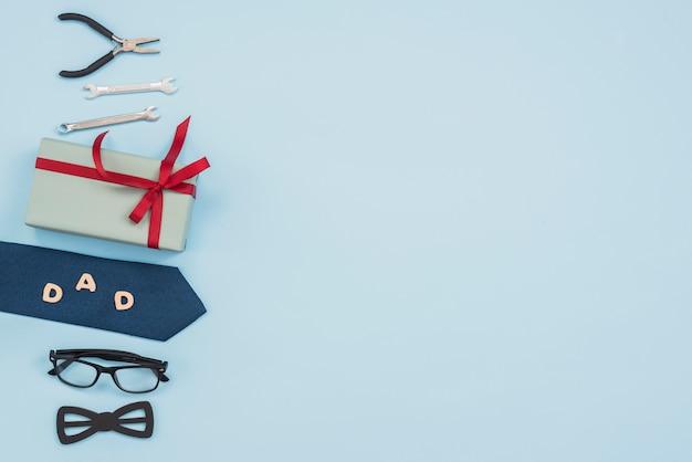 Inscripción de papá con caja de regalo, herramientas y corbata. Foto gratis