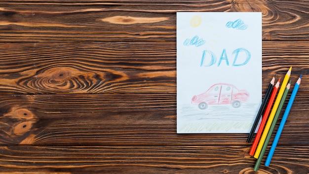 Inscripción de papá con dibujo de coche en hoja de papel Foto gratis