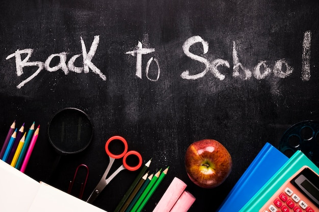 Inscripción de regreso a la escuela y papelería en la pizarra. Foto gratis