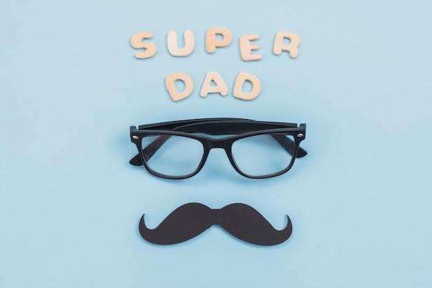 Inscripción de super papá con gafas y bigote negro. Foto gratis