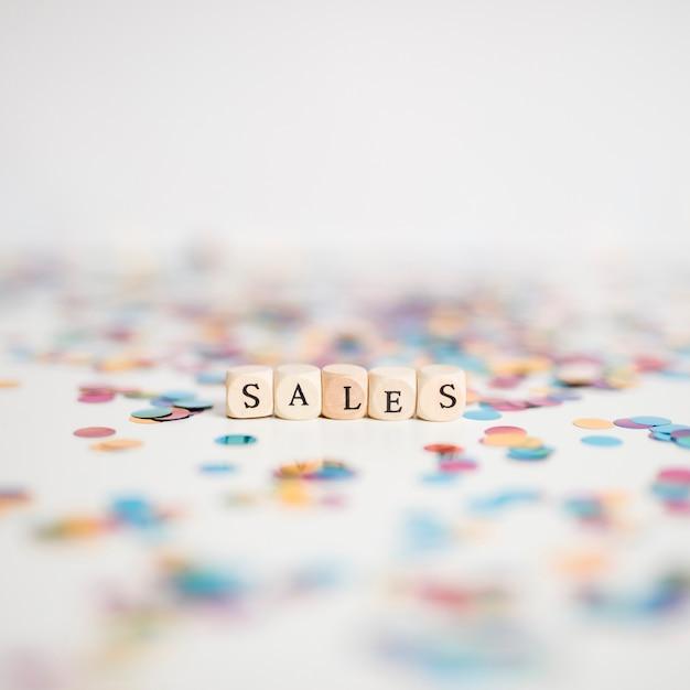 Inscripción de ventas en pequeños cubos con confeti. Foto gratis